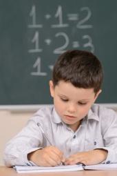 Confident little boy writing somethi